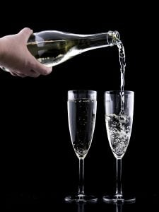 Two glasses of sparkling wine being poured by a caucasian male on a black background | Luxury Homes by Brittany Corporation