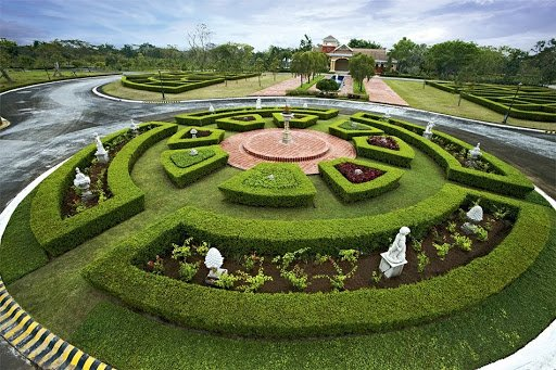 Outdoor circular shaped grassy courtyard with hedges, marble statues, flowers, potted plants, growing ferns, and a bricked centerpiece with a tall marble pot or fountain   Luxury Homes by Brittany Corporation
