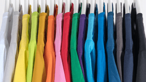 Rainbow colored closet with colorful shirts on grey hangers in a white cabinet | Luxury Homes by Brittany Corporation