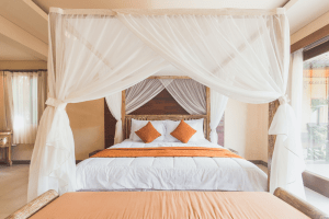 White queen size bed with orange pillows and a wooden bed frame with thin white drapes in a spacious bedroom with an orange couch and a curtained doorway leading to an outdoor courtyard | Luxury Homes by Brittany Corporation