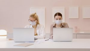 Two women working on their laptops while socially distanced and with masks on as an effect of the Covid-19 pandemic | Luxury Homes by Brittany Corporation