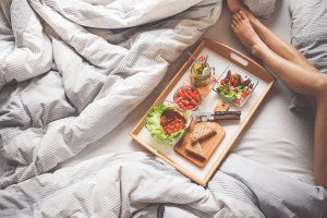 Olive skin tone legs next to a wooden tray with a healthy green breakfast of salads, fruits and berries, whole wheat sandwiches, and a mason jar of green tea with a metal straw, on a king size bed with striped blue and white duvet | Luxury Homes by Brittany Corporation