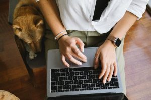 A woman working remotely at home in her own space with her pet Shiba Inu | Luxury Homes by Brittany Corporation