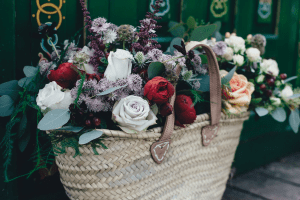 A woven basket bag with leather handles, filled with dainty and colorful roses, vines, leaves, and berries | Luxury Homes by Brittany Corporation