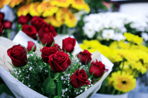 A bouquet of red roses wrapped in white paper, with a background of other bouquets of yellow and white flowers   Luxury Homes by Brittany Corporation