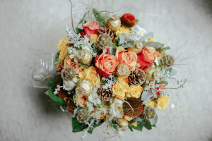Top view of colorful flower arrangement with roses, twigs, pinecones, and ornaments | Luxury Homes by Brittany Corporation