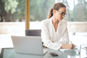Beautiful brunette woman with glasses and red lipstick, wearing a white blazer while jotting down notes during an online webcam meeting through her laptop | Luxury Homes by Brittany Corporation