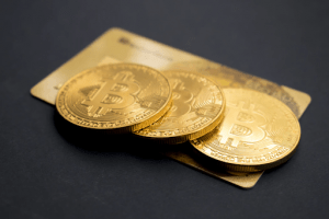 Bitcoin coins laid out on top of a credit card in a luxury home | Luxury Homes by Brittany Corporation