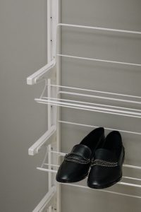 Black leather loafers with silver chain accent, displayed on a white shoe rack | Luxury Homes by Brittany Corporation