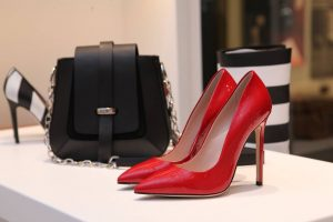Bright scarlet red stiletto heels next to a black leather shoulder bag with a silver chain handle, on a white platform display inside a store | Luxury Homes by Brittany Corporation