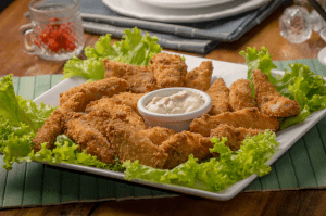 Chicken tenders, cooked in an air fryer which is one of the trendy new home items, on a bed of lettuce, with ranch dressing | Luxury Homes by Brittany Corporation