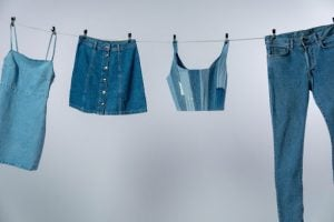 Dress, buttoned skirt, patchy crop top, and pants or jeans all made of denim material or cloth, all hung on a clothesline inside a white room | Luxury Homes by Brittany Corporation