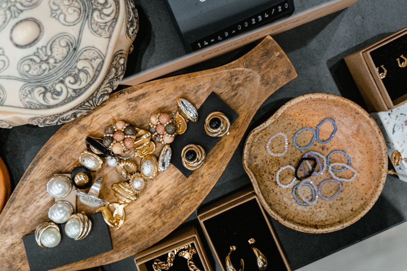 Stone jewelry of rings, bracelets, earrings, and necklaces, on display on thick wooden plates.