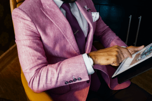 Formal attire of thick pink tweed coat over a polka dotted shirt and violet tie on a tan man with a classy watch and accessories, using his iPad for browsing the internet | Luxury Homes by Brittany Corporation