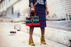 Figure of a black woman wearing high fashion clothes in different patterns and colors: checkered blazer, striped shirt, plaid knee-length skirt, fishnet stockings, bright yellow strappy heels, and striped bright handbag; standing in a dodgy area | Luxury Homes by Brittany Corporation