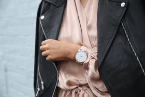 Leather jacket on silky rose gold dress and rose gold watch worn by an olive skin girl for power dressing in her workplace | Luxury Homes by Brittany Corporation