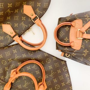 Top view of Louis Vuitton bags of different shapes and sizes against a white surface, including a hand bag and a backpack | Luxury Homes by Brittany Corporation