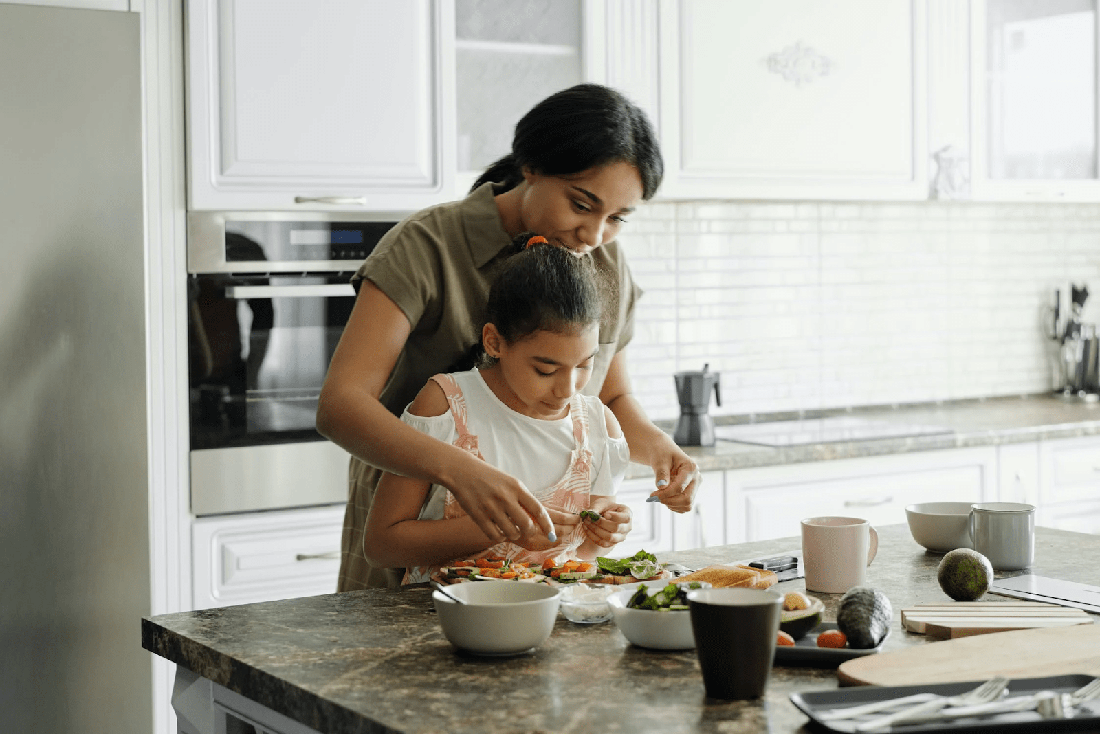Middle Eastern mother helping child prepare breakfast in a white kitchen | Luxury Homes by Brittany Corporation