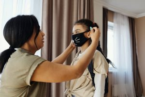 Mother putting facemask on daughter as they stay safe in their luxury home | Luxury Homes by Brittany Corporation
