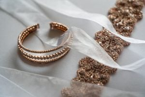 Rose gold choker necklace and bangles with rhinestones on a white surface, covered by tulle ribbons | Luxury Homes by Brittany Corporation