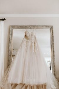 Dainty peachy white classic wedding dress in layers of tulle and embroidered classic details, hanging from a clear plastic hanger hooked on to a tall grand mirror with a classic frame inside an elegant room