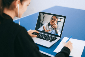 Woman having an online webcam meeting with an old lady, while taking down notes | Luxury Homes by Brittany Corporation