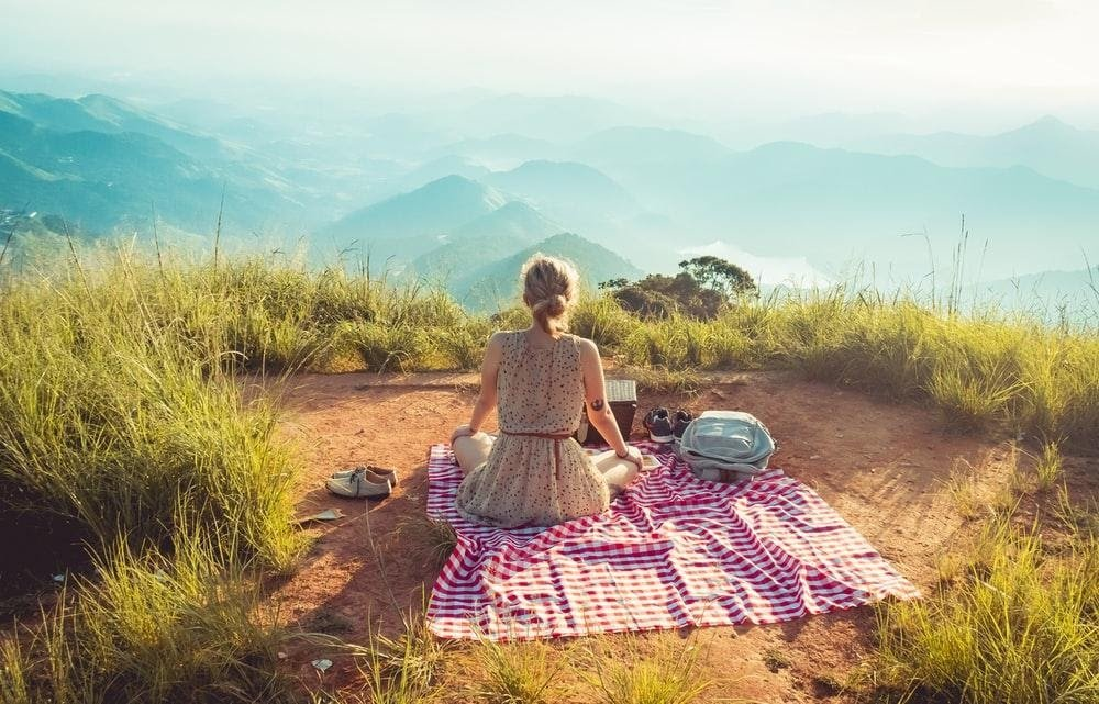 woman sitting on top of a hill with table cloth and picnic basket in Swiss-inspired luxury village in Tagaytay | Luxury Homes by Brittany Corporation
