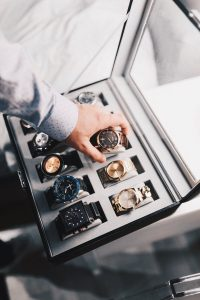 Hand of a man wearing a long sleeved formal shirt, reaching for a classic expensive watch from a leather case collection of other branded timepieces like Rolex | Luxury Homes by Brittany Corporation