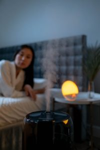 A black humidifier puffing out steam inside a bedroom in the evening, with a background of a woman wearing a robe in bed, next to a night lamp on a beside table