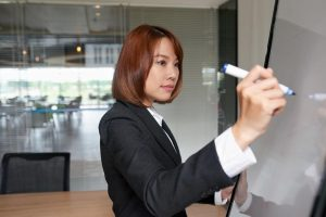 Asian woman with short auburn hair wearing professional attire, writing her growth mindset plans on a whiteboard in a conference room of an office | Luxury Homes by Brittany Corporation