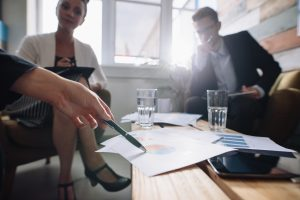 Shot of business people in a meeting at office, with woman pointing at charts with travel advisor. Corporate professional discussing financial growth of the company | Luxury Homes by Brittany Corporation
