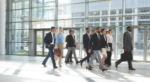 A group of multiracial real estate sales professionals walking together towards the same direction inside a modern building.