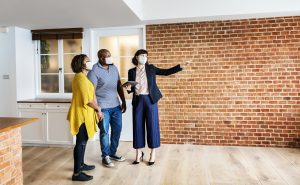 A black couple being toured by a white real estate broker in a professional outfit, around a modern industrial home with bricked walls and white kitchen   Luxury Homes by Brittany Corporation