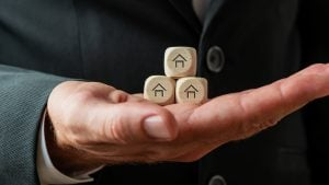 Hand of a businessman or realtor holding three wooden dices with house shapes on them   Luxury Homes by Brittany Corporation