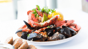 A fresh bowl of seafood marinara served on a white platter | Luxury Homes by Brittany Corporation