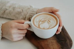 A freshly brewed cup of coffee on a wooden platter for serving | Luxury Homes by Brittany Corporation