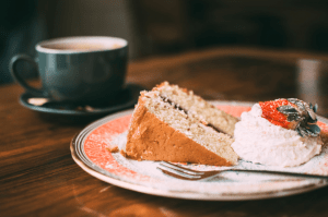A plate of sliced strawberry shortcake with strawberry on icing, next to a cup of hot coffee, all on a wooden table - Luxury homes for sale - Brittany Corporation