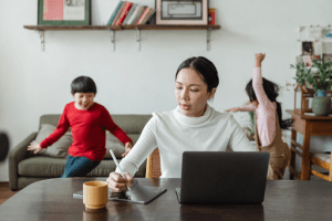 Asian mother working from home while her two children are playing in the living room of their luxury home | Brittany Corporation