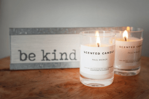 Branded scented lit candles with simple packaging, next to a sign that says be kind