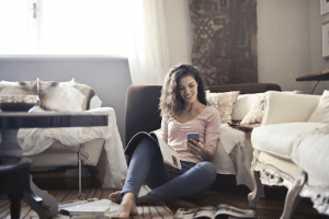 Brown haired Scandinavian woman looking at magazines and her phone in comfortable clothes, sitting on the living room floor during the rainy season