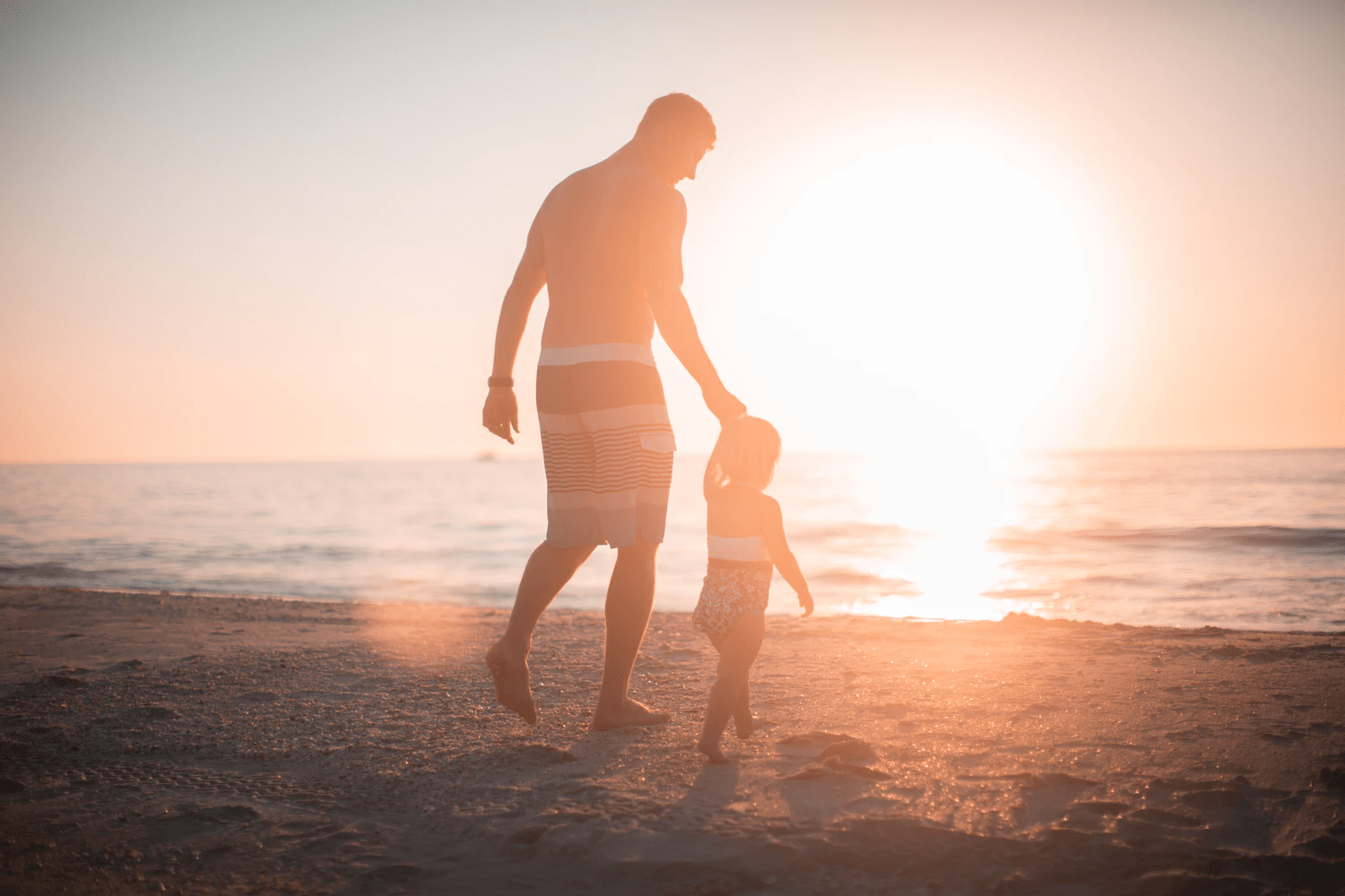 Father and son walking along the shore of a beach during sunset | Brittany Corporation