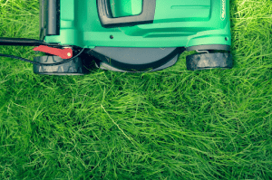 Lawnmower trimming fresh green grass Luxury Homes by Brittany Corporation