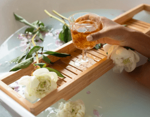 Pamper yourself with milk bath filled with flowers, while female person is drinking from a chalice in the bathtub - Luxury homes for sale - Brittany Corporation