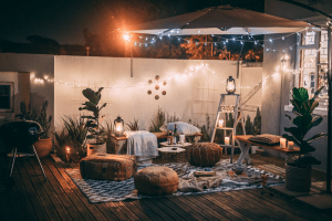 Outdoor porch chill cozy vibe setup with hanging fairy lights and boho furniture perfect for the rainy season | Luxury Homes by Brittany Corporation