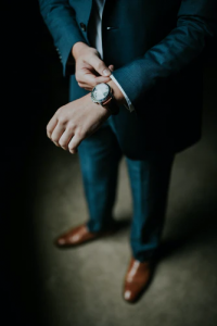 Young professional male adjusting in a navy blue three piece suit with brown leather shoes adjusting his watch before getting ready to leave his luxury home in the Phlippines   Brittany Corporation