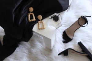 Stiletto heels and luxury jewelry on a white fur carpet in a luxury home by Brittany Corporation