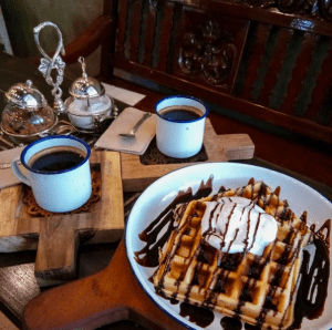 Two cups of freshly brewed coffee paired with a couple of waffle topped ice cream dish | Luxury Homes by Brittany Corporation