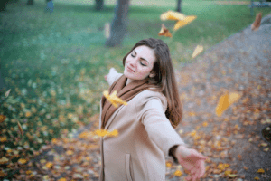 Woman pamper herself while twirling around in a nature park with falling leaves near her luxury home for sale - Brittany Corporation