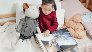 Young child playing with her sheep plush toy while reading a childrens book about space in her luxury home | Brittany Corporation