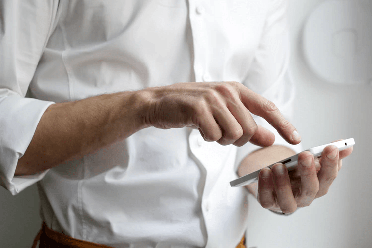 Young real estate sales professional using his phone to check the stock market | Luxury Homes by Brittany Corporation